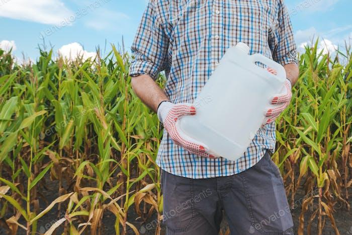 Farmer holding pesticide chemical jug in cornfield