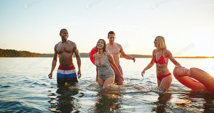 Diverse friends wearing swimsuits having fun together in a lake