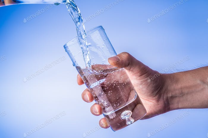 Filling up the glass with water, hand holding glass against bright blue background