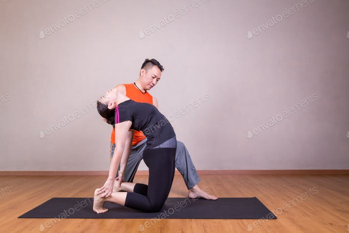 Yoga instructor guiding student perform Camel pose or Utrasana