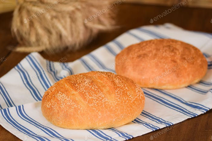 Freshly baked traditional bread on wooden table.