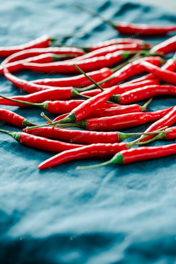 Macro photography of chili peppers on a blue linen.