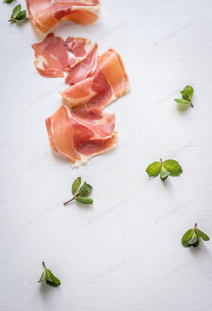 Slices of jamon on the white background
