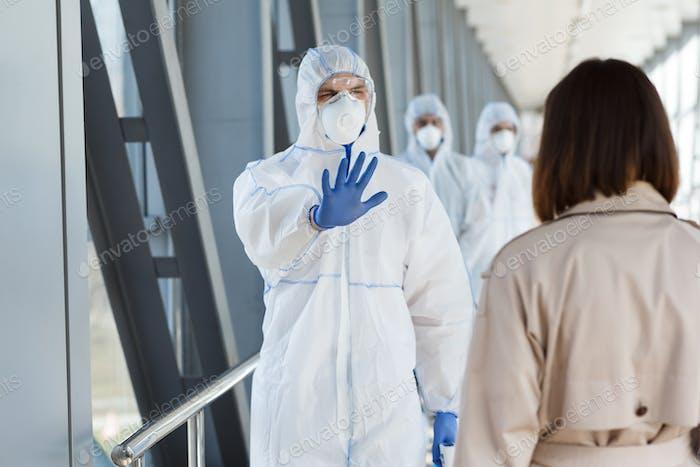 Medizinischer Arbeiter zeigt Stoppzeichen an Frau