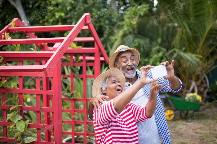 Cheerful couple taking selfie while standing in yard