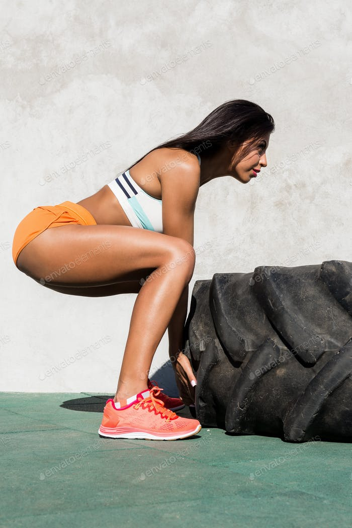 Crossfit girl exercise with big tire.