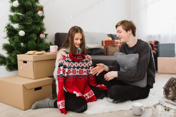 Beautiful girl holding new sweater while sitting with boy on floor at home near Christmas tree