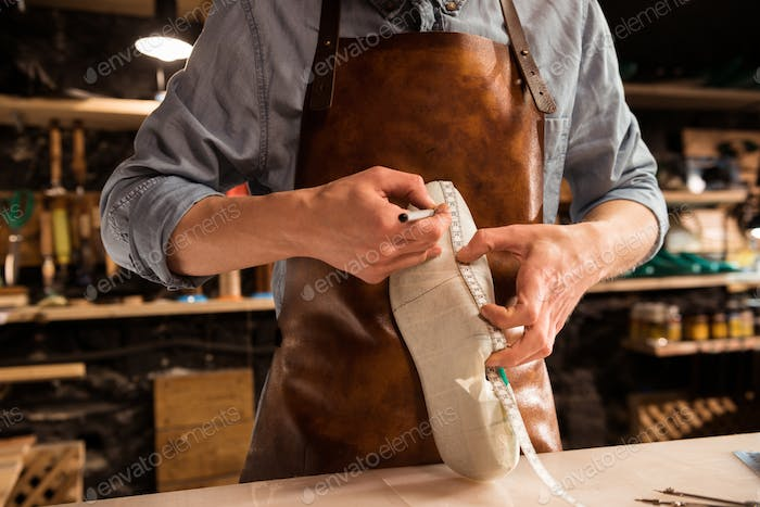 Cropped image of a shoemaker measuring a shoe