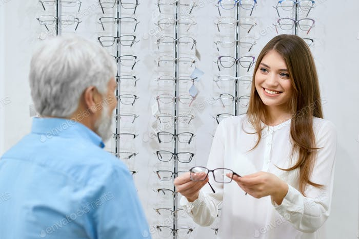 Beatiful smiling assistant showing eyeglasses to old man