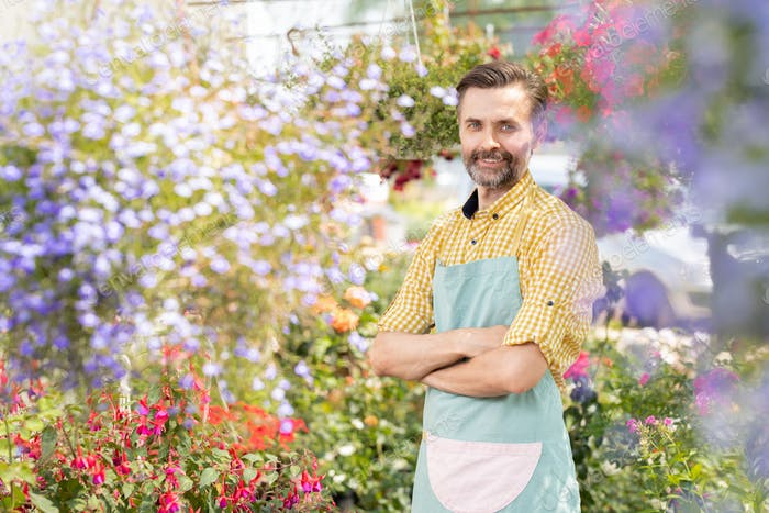 Happy male gardener crossing his arms by chest while looking at camera