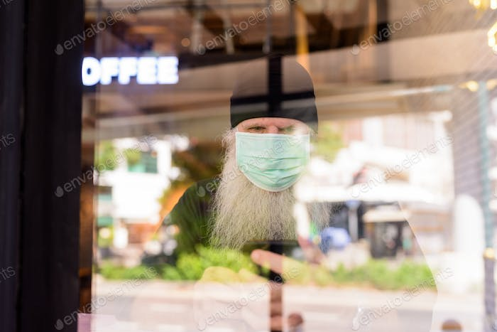 Mature bearded hipster man with mask using phone at the coffee shop through the window