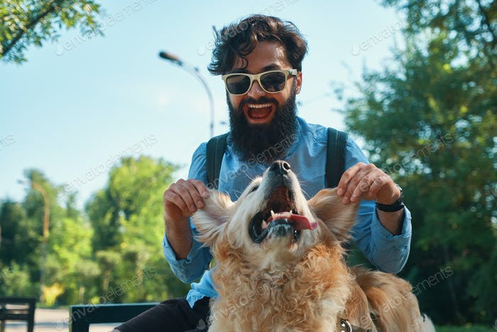 Man and dog having fun, playing, making funny faces while restin