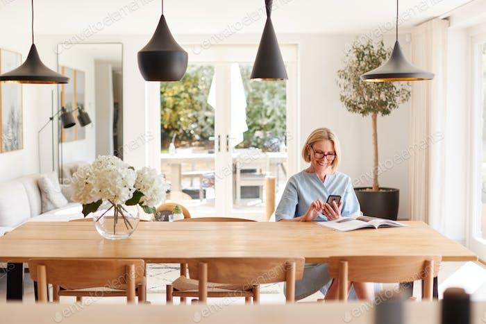 Senior Frau Entspannend Mit Magazin Zu Hause Blick Auf Handy sitzen Am Esszimmer Tisch