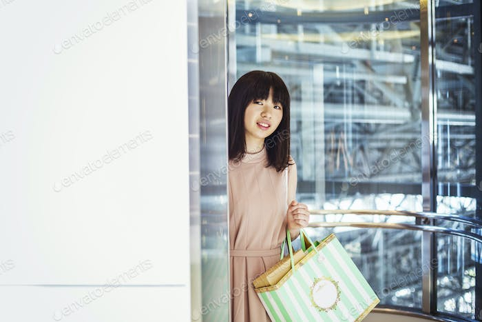 Young woman with long brown hair in a shopping centre, carrying shopping bags.