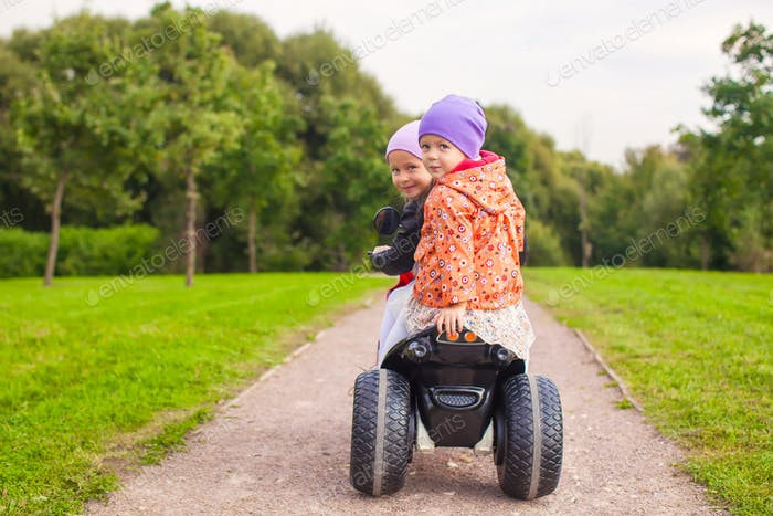 Portrait of adorable little girls ride a motorbike in green park