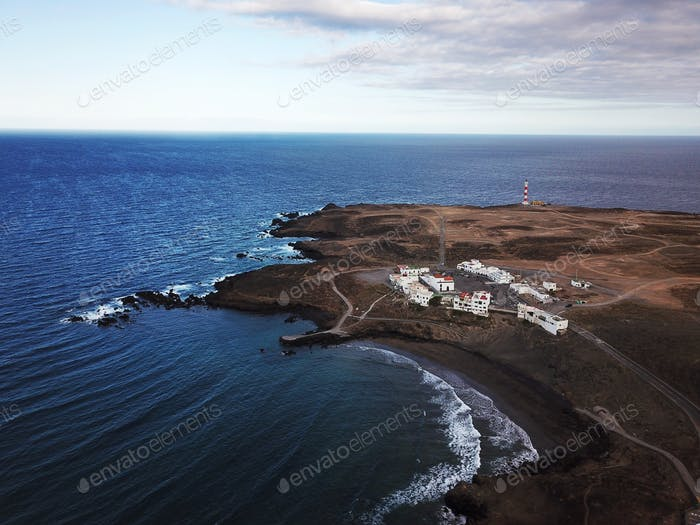 View from the height of rocky coastline with white buildings and