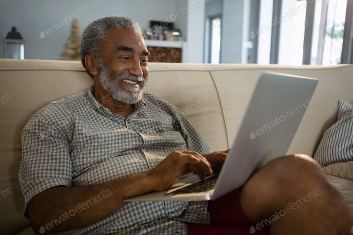 Senior man using laptop in the living room