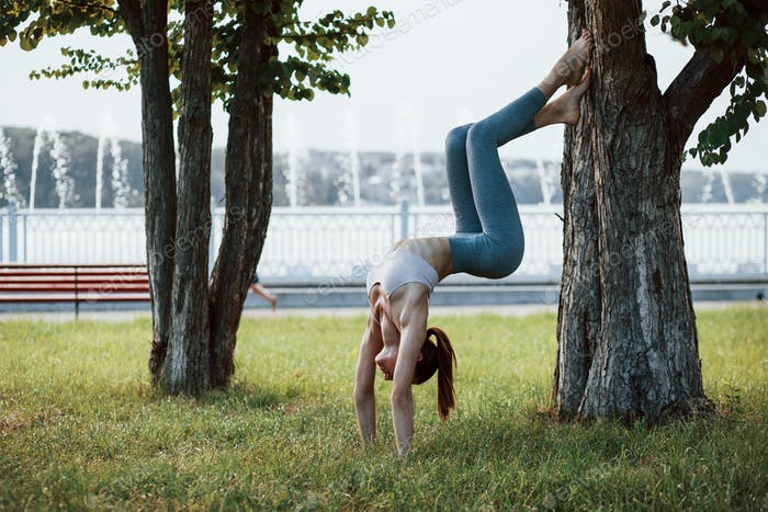 Awesome flexibility. Young woman with slim type of body does exercises in the park
