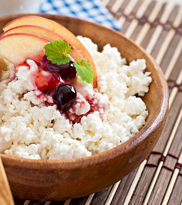 Cottage cheese with apple, berry syrup and sour cream for breakfast in wooden bowl close up