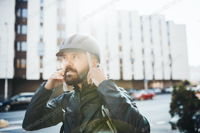 Male courier putting on a helmet when delivering packages in city.