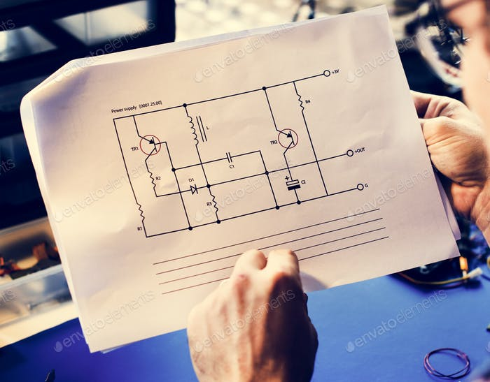 Closeup of hands holding circuit pattern guide line paper