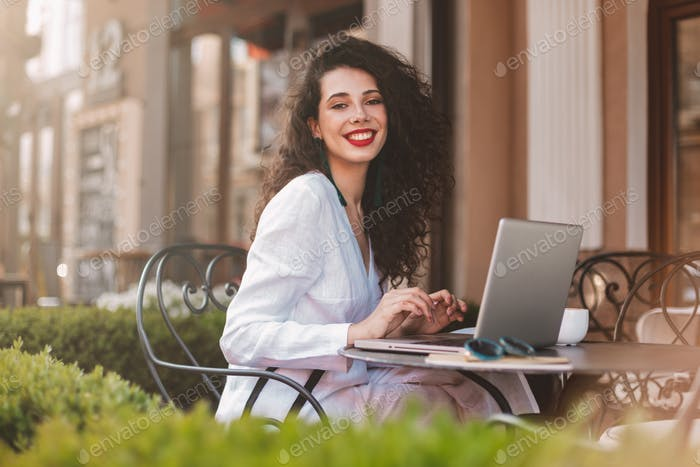 Pretty smiling lady in white costume sitting in street cafe with laptop happily looking in camera