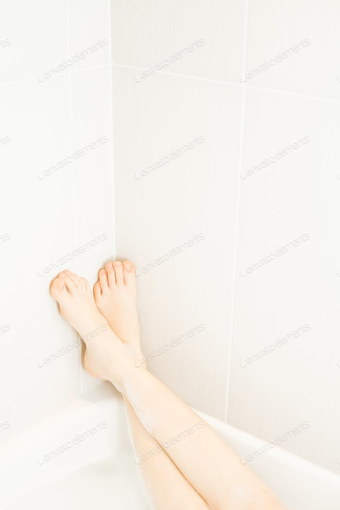 Woman legs in the corner of the bath