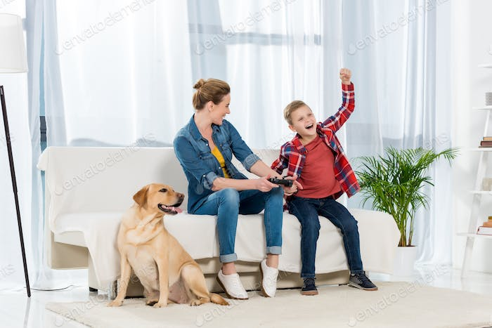 mother and happy little son playing video games while their dog sitting on floor