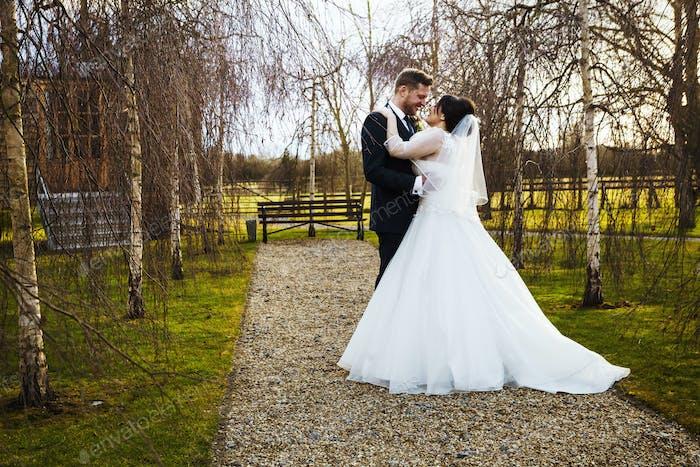 Eine Braut und Bräutigam Hand in Hand, an ihrem Hochzeitstag, in einem Garten.