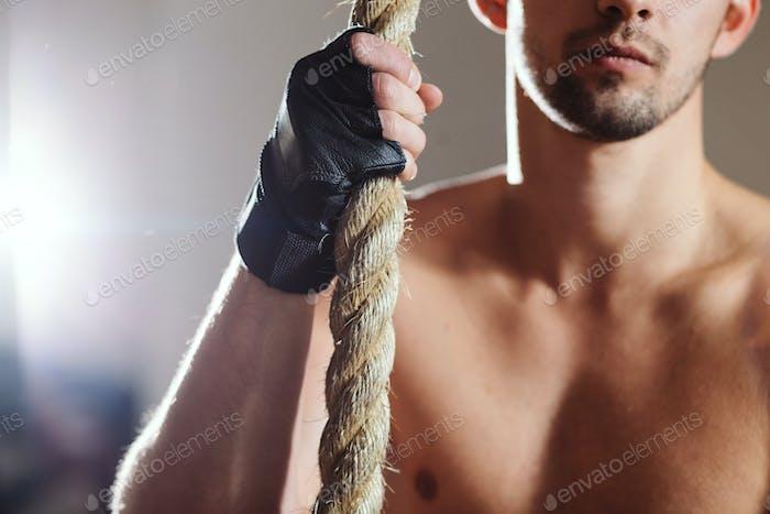 rope climbing workout athlete man in gym