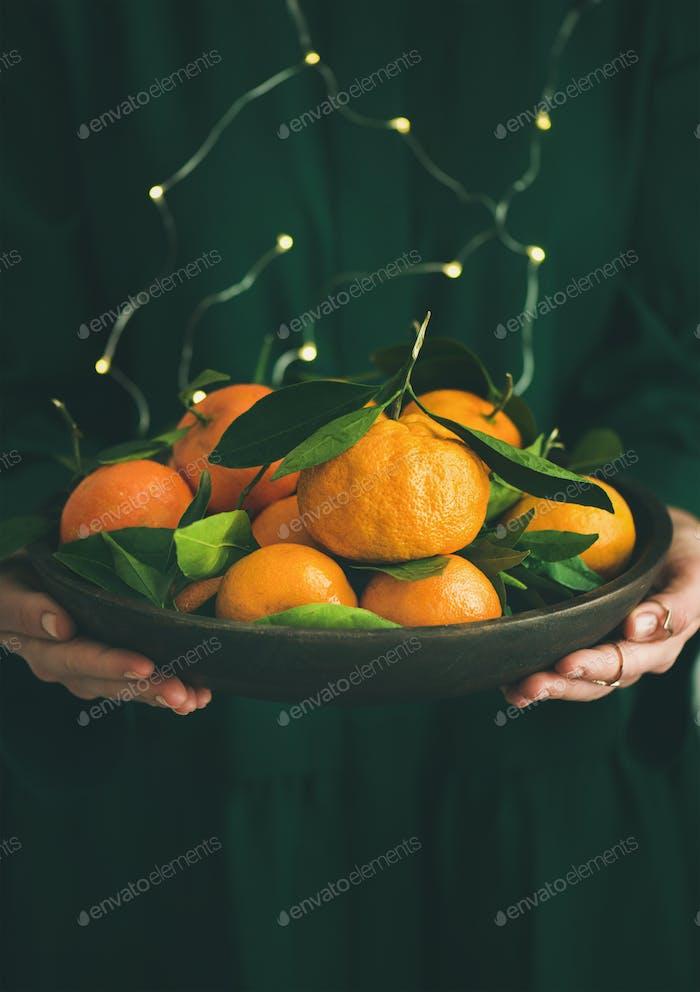 Fresh tangerine fruit in plate in female hands