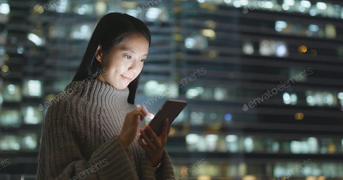 Frau senden SMS auf Handy am Abend