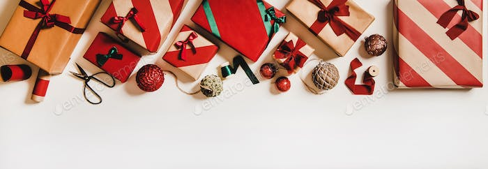 Flat-lay beije, green and red color craft gift boxes and Christmas decorations
