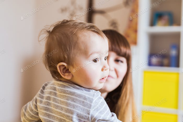 Close-up portrait of happy mother with adorable baby boy indoors