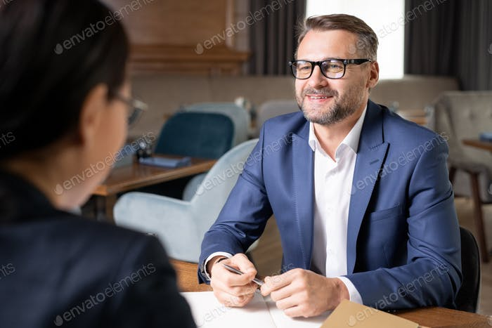 Happy confident businessman in formalwear and eyeglasses looking at colleague