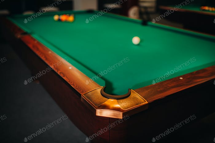 decorative billiard hole and green table with balls in the billiard club