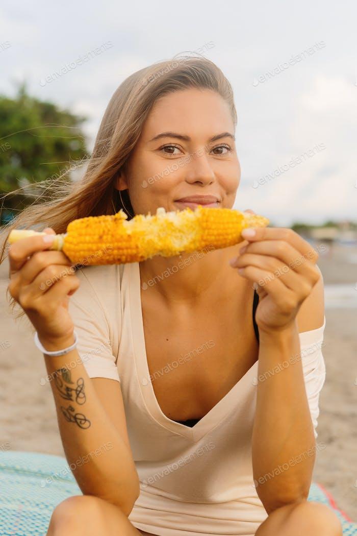Beautiful vegetarian girl eat corn at seaside.
