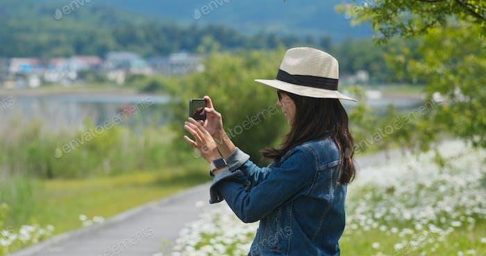 Frau nimmt Foto mit Handy auf dem Land