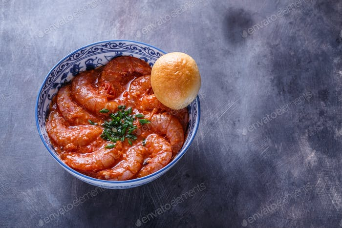 Bowl of shrimps in spicy tomato sauce, singaporean cuisine, copyspace