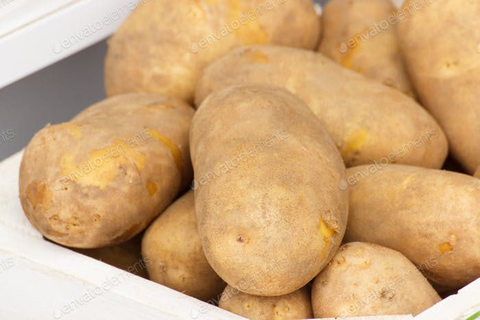 Fresh potatoes in wooden box, healthy nutrition concept