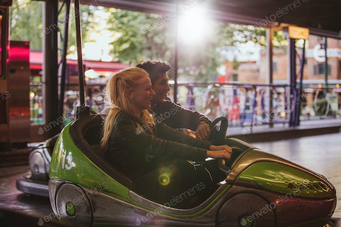 Happy young couple driving a bumper car at amusement park