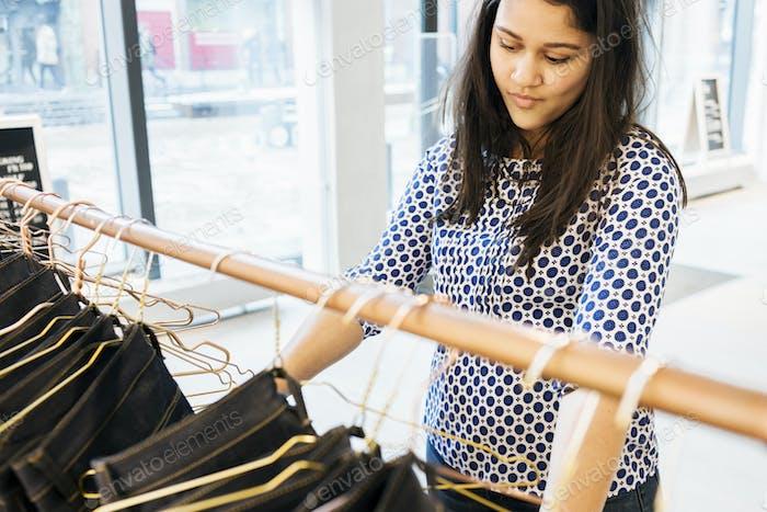 Confused woman choosing jeans in factory