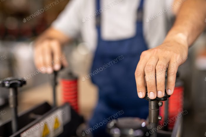 Hand of technician or engineer turning one of handles of industrial equipment