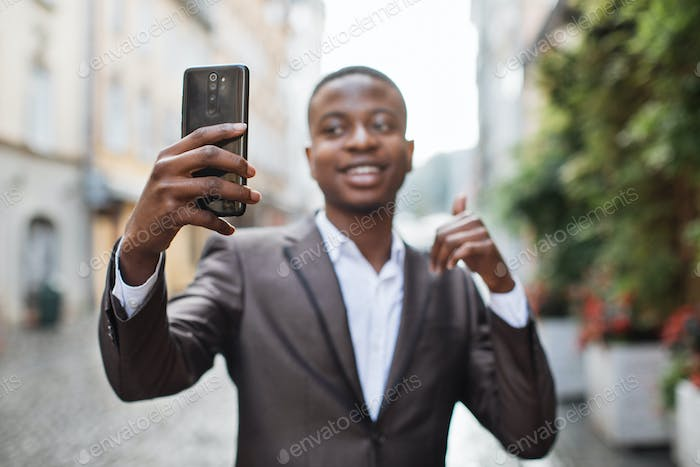 Happy afro businessman using smartphone for video chat