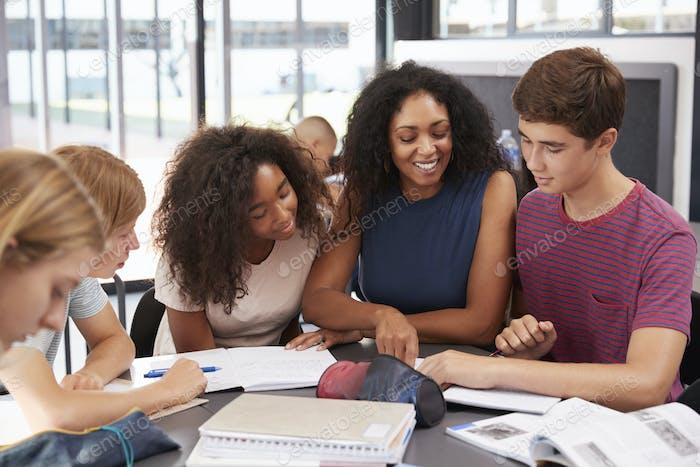 Lehrer studieren Schulbücher in der Klasse mit High-School-Kinder