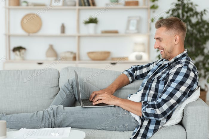 Happy man chatting online on laptop with friend at home