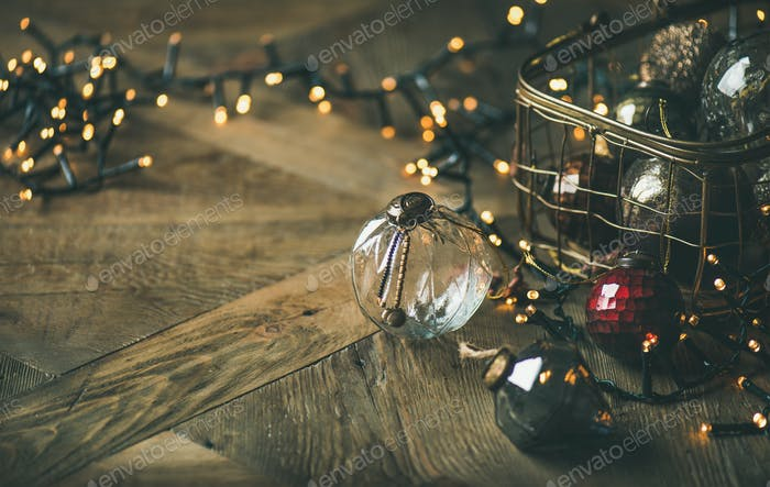 Christmas decoration balls in box and light garland, copy space