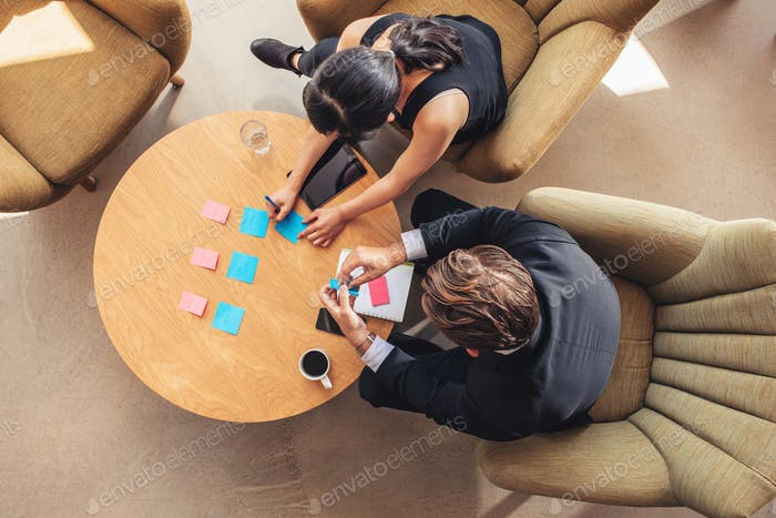 Businesspeople discussing over adhesive notes in office lobby