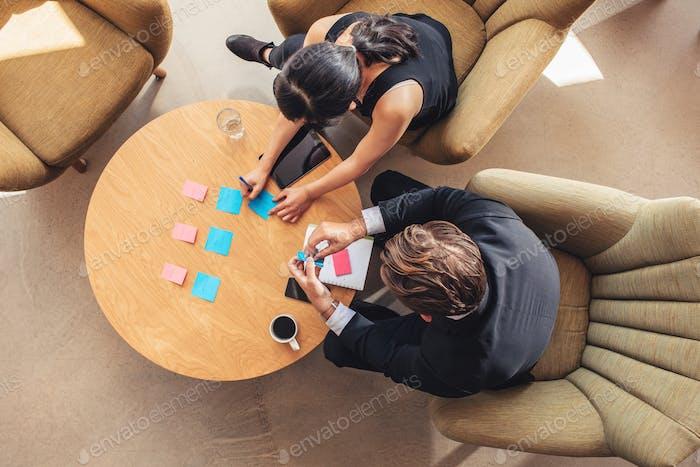 Geschäftsleute diskutieren über Haftnotizen in der Bürolobby