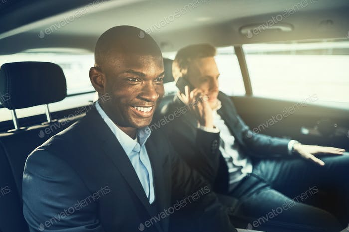 Smiling African businessman driving with a colleague to work